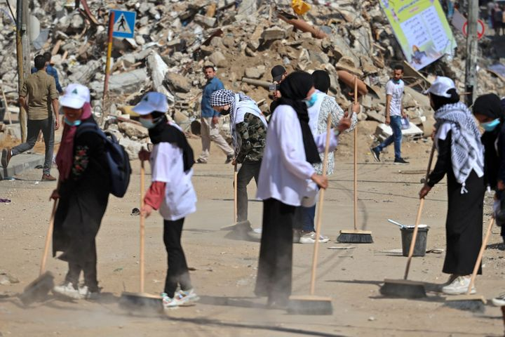 Palestinian volunteers sweep the rubble of buildings, recently destroyed by Israeli strikes, in Gaza City's Rimal district on