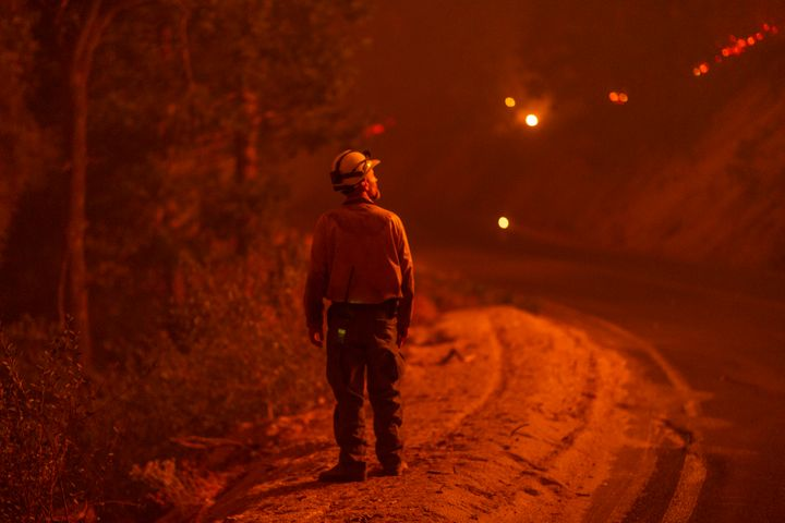 A firefighter keeps watch as flames advance along the Western Divide Highway during the SQF Complex Fire on September 14, 202