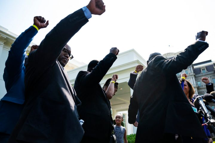 George Floyd's family and their lawyer Ben Crump, right, hold up their fists outside the White House as Floyd's daughter Gian