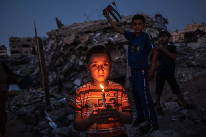 Palestinian children hold candles during a vigil Tuesday amid the ruins of houses in Beit Lahia, Northern Gaza Strip. Gaza re