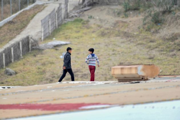 Dos niños caminan por el tejado de una nave en el Tarajal (Ceuta), el 20 de mayo de