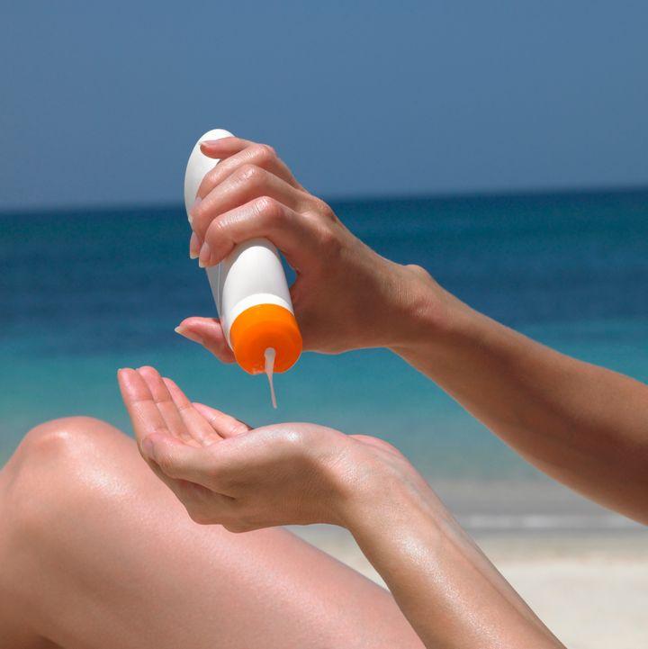 Una mujer se aplica crema solar en la playa.