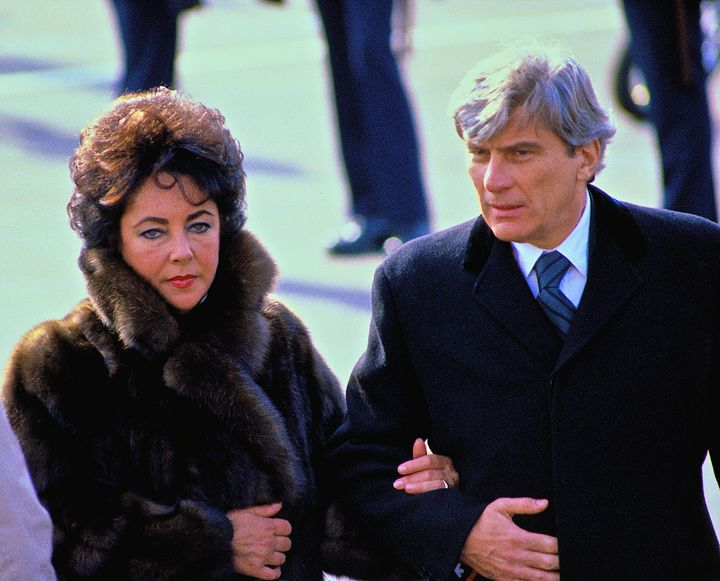 John Warner (right) and his then-wife Elizabeth Taylor seen leaving the swearing in of President Ronald Reagan in 1981. (Photo by Mark Reinstein/Corbis via Getty Images)