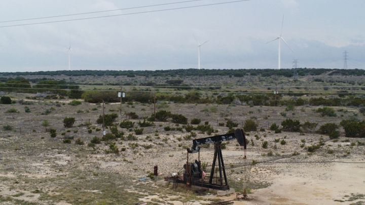 Blades from wind turbines rotate in a field behind an out-of-use oil pumpjack last month near Eldorado, Texas.