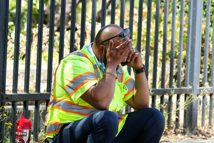 A man cries while sitting on the sidewalk near the scene of a mass shooting at the Valley Transportation Authority's (VTA) li