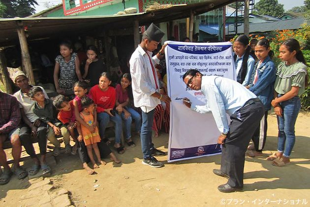 ネパール・バンケ郡のコミュニティで、早すぎる結婚の防止に賛同し署名する行政職員