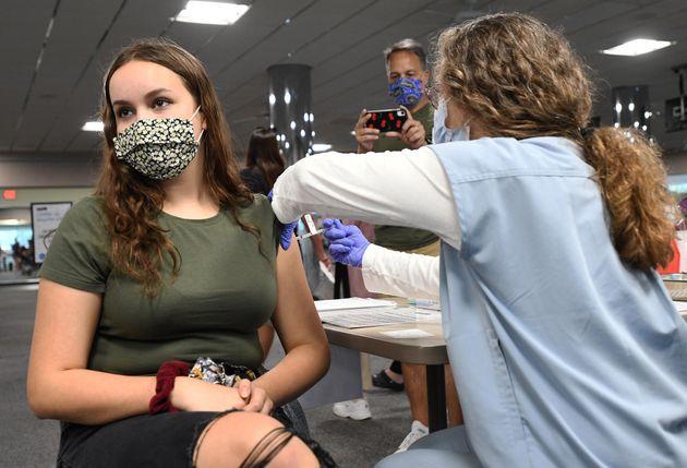 Una enfermera administra la vacuna de Pfizer a un chica de 15 años en