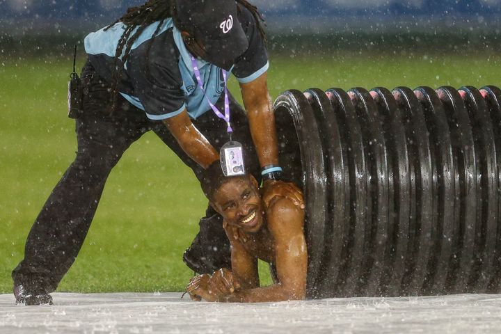 A streaker is pulled from the infield tarp roller tube by security during a rain delay between the Cincinnati Reds and agains