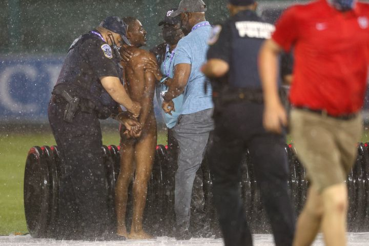 A streaker is arrested by law enforcement and security during a rain delay between the Cincinnati Reds and against the Washin