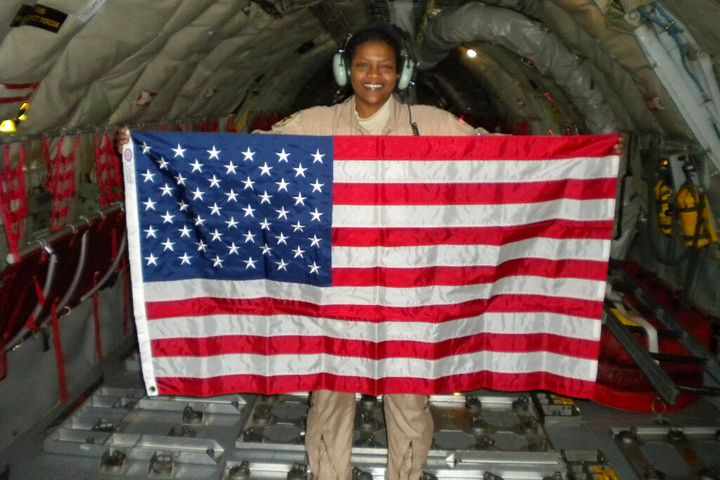 Retired Air Force Lt. Col. Stephanie Davis holds a U.S. flag in the cargo area of a KC-135 airplane while flying over Pakista