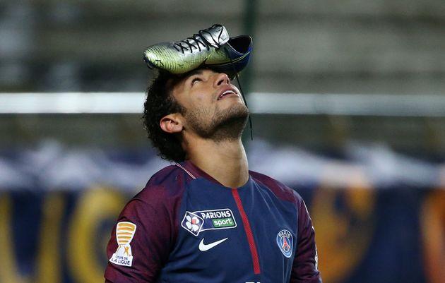 Neymar, celebra un gol en un partido de la liga francesa, sosteniendo una zapatilla de la marca Nike,...
