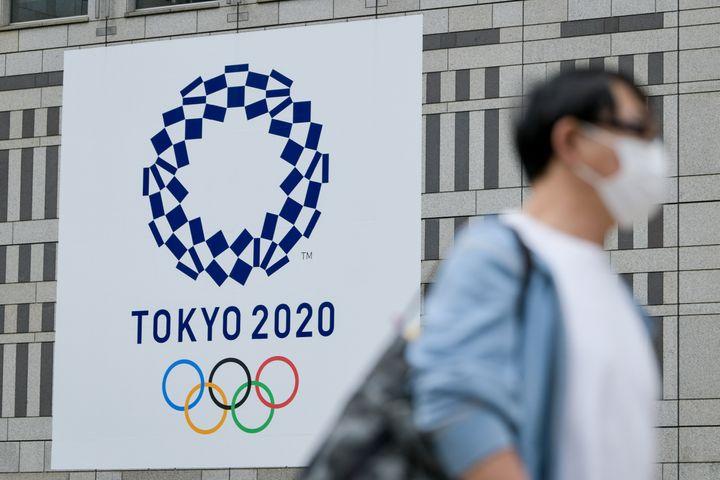 Мужчина проходит мимо плаката Токио-2020 на здании в районе Синдзюку в Токио.