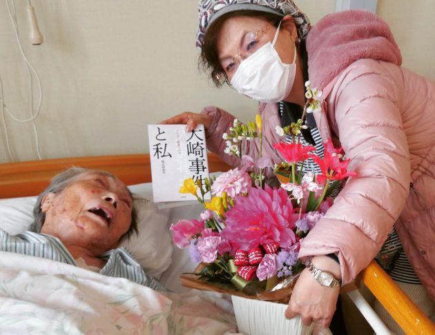 原口アヤ子さんを見舞う鴨志田祐美弁護士。アヤ子さんと共に歩んだ再審請求の戦いを描いた自著を携えた=2021年3月21日