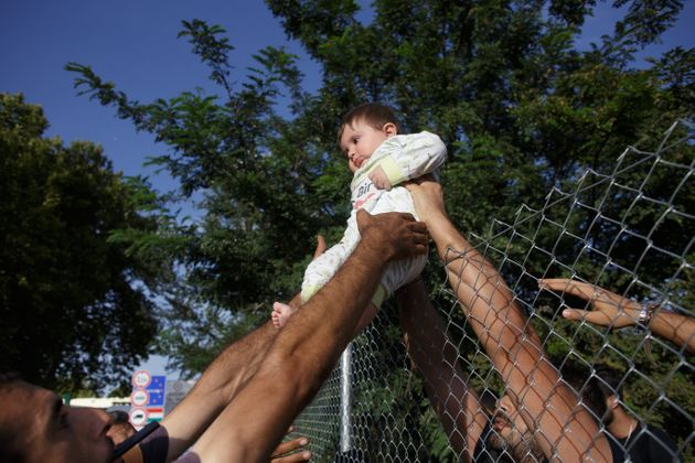 Serbia, Horgos. Group of refugees crossing holding baby over wired fence short after closing Hungarian