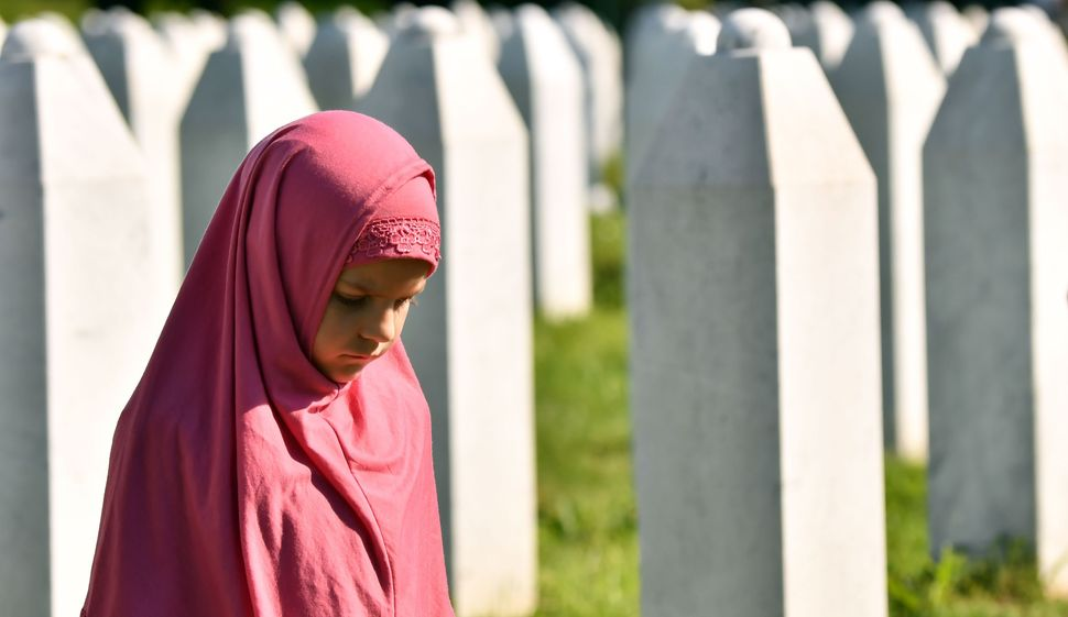 Una bambina musulmana bosniaca cammina tra le lapidi dei suoi parenti, al cimitero commemorativo di Potocari,...