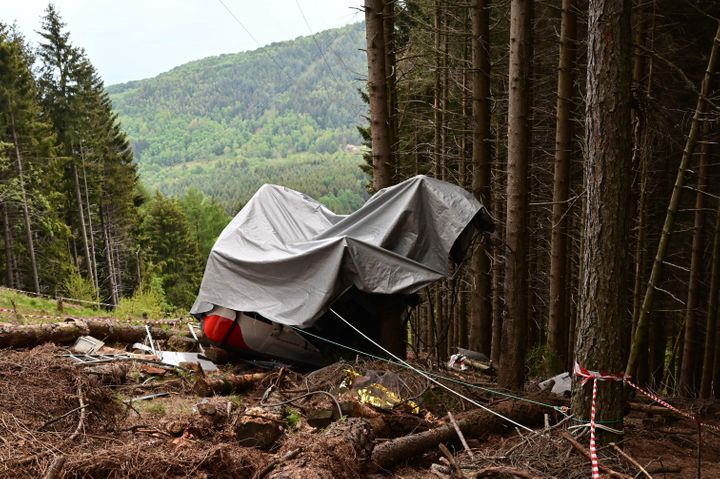A view shows the cabin's wreckage covered with a tarpaulin on May 26, 2021 on the slopes of the Mottarone peak above Stresa,