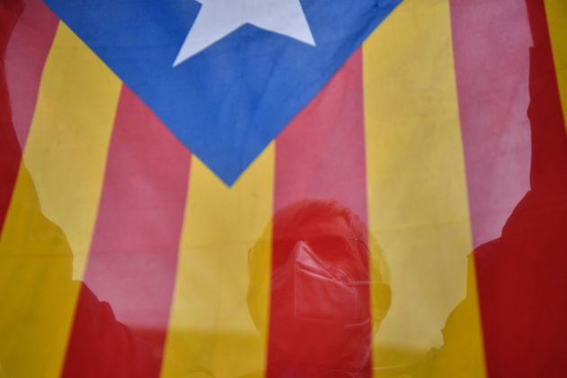 TOPSHOT - A man holds up a Catalan pro-independence Estelada flag during a demonstration called by the...