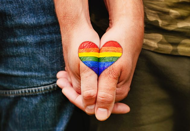 Rainbow heart drawing on hands, LGBTQ love symbol, gay couple hand in hand, homoseaxual