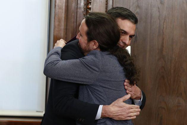 Pedro Sánchez y Pablo Iglesias se abrazan tras firmar el pacto que armó la coalición de Gobierno, el...