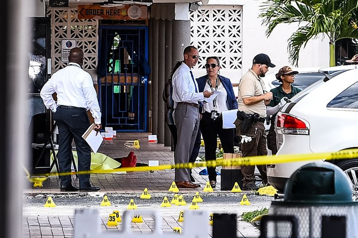 Miami Dade police officers are seen at the scene of a mass shooting that left two people dead and 21 others injured.A r