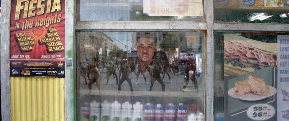 """Usnavi (Anthony Ramos) looks through the window of his bodega in a scene from """"In the Heights."""""""
