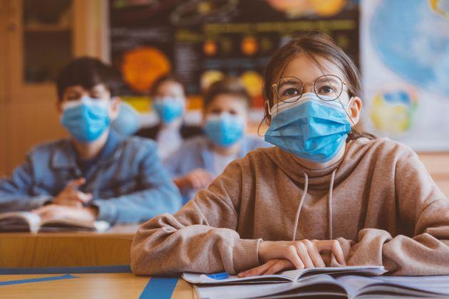 High school students at school, wearing N95 Face masks. Teenage girl wearing eyeglasses sitting at the...