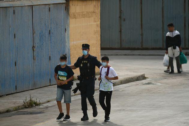 Agentes de la Policía Nacional acompañando a menores llegados a Ceuta, en la frontera de El
