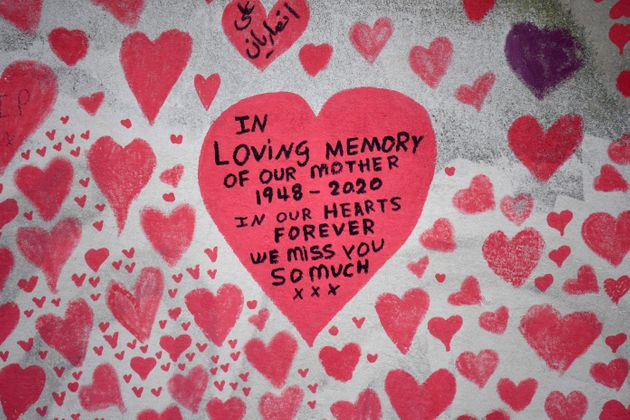 Messages are pictured on hearts painted on the National Covid Memorial Wall, at the embankment on the...