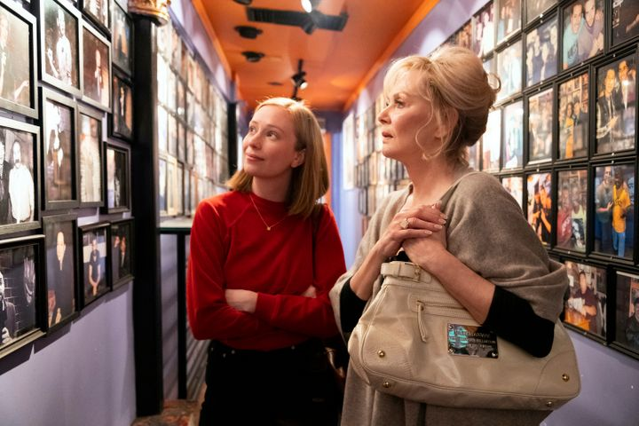 Ava (Hannah Einbinder) (left) and Deborah (Jean Smart) (right) looking at an old photo of Deborah on the wall at a comedy clu