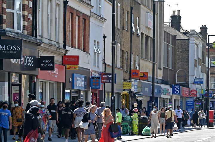 Pedestrians, some wearing face covering due to Covid-19, walk past shops in Hounslow, west London on June 1, 2021.