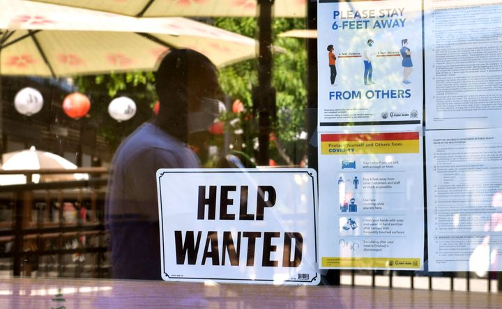 A 'Help Wanted' sign is posted beside Coronavirus safety guidelines in front of a restaurant in Los Angeles, California on Ma