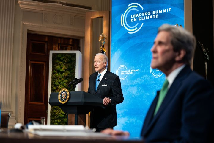 President Joe Biden delivers remarks as John Kerry, special presidential envoy for climate, listens at the virtual Leaders Su