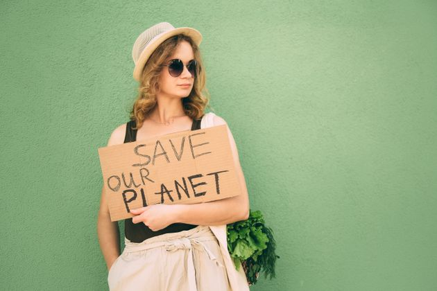 Beautiful blonde girl showing save our earth drawing on the brown carton paper over green