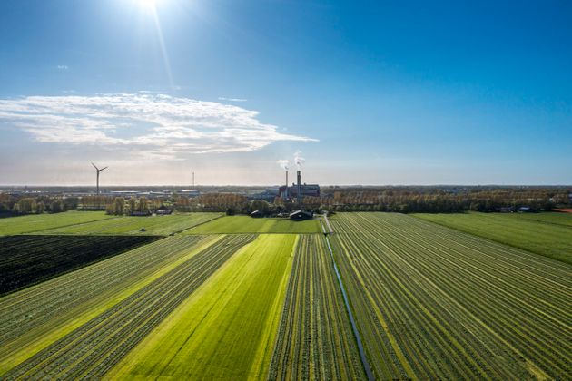 Factory with tall chimney in a green landscape, the