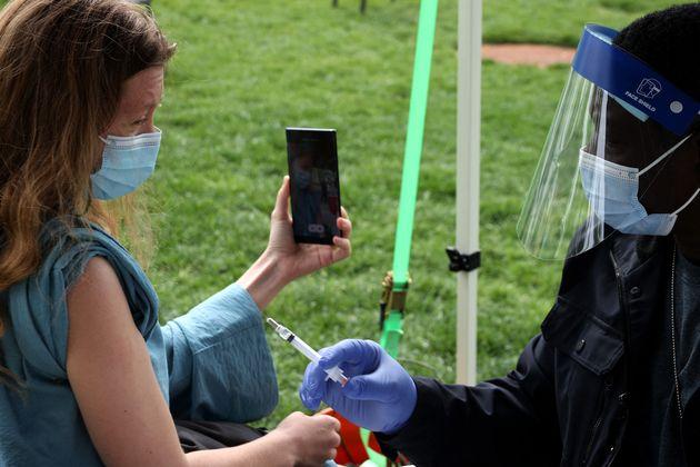 Une personne se filme en train de se faire vacciner à Washington, aux États-Unis, où est offert une bière gratuite aux volontaires (photo prise le 6 mai 2021).