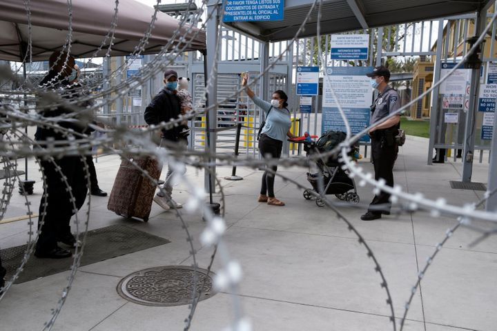 An asylum seeker waves goodbye a she enters the United States at a port of entry.