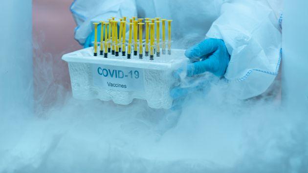 파란 장갑과 보호장비를 갖춘 의료진이 병원 코로나19구역 냉동 창고에 보관 중인 백신 박스를 제거하고