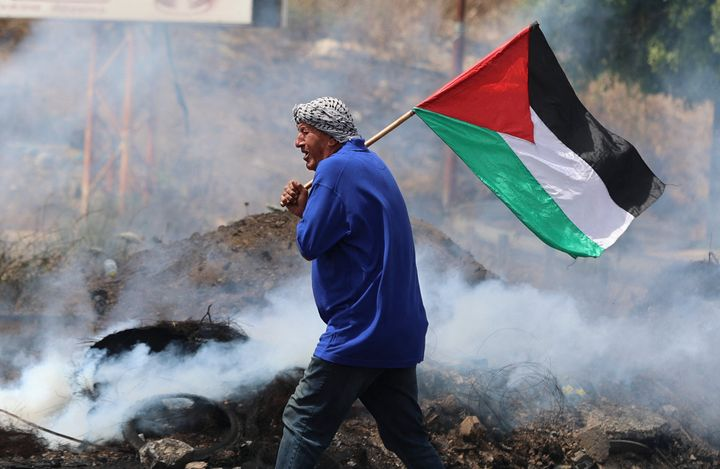 A Palestinian protester lifts a national flag amid confrontations with Israeli security forces at the Hawara checkpoint south