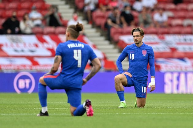 England midfielders Kalvin Phillips (L) and Jack Grealish (R) take the knee ahead of the international...