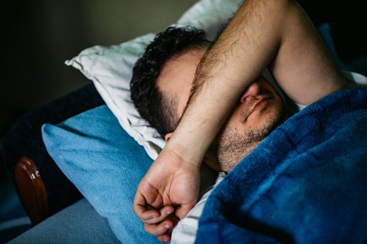 Young Caucasian man waking up in bed in late morning.
