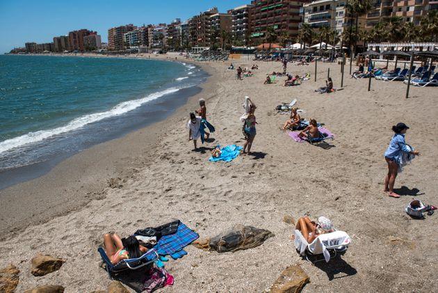 Un grupo de turistas toma el sol en la playa de