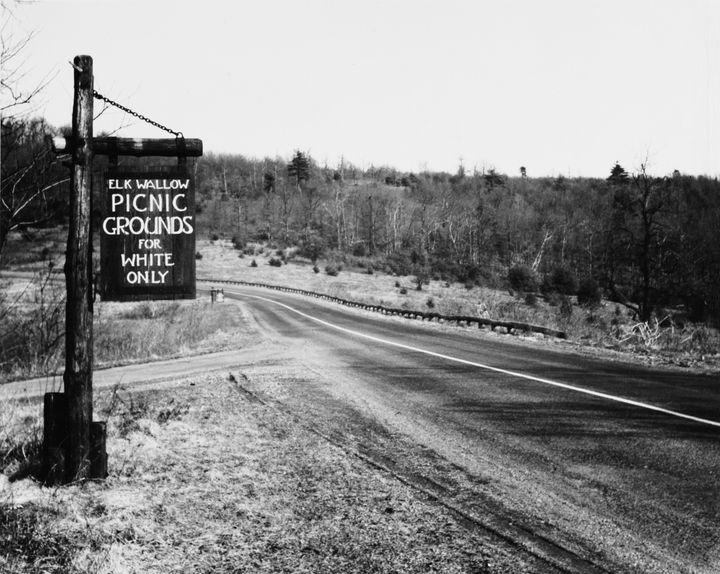 """A sign at Elkwallow Picnic Grounds in Shenandoah National Park, Virginia, reads """"Picnic grounds for white only"""" in 1940. Afte"""