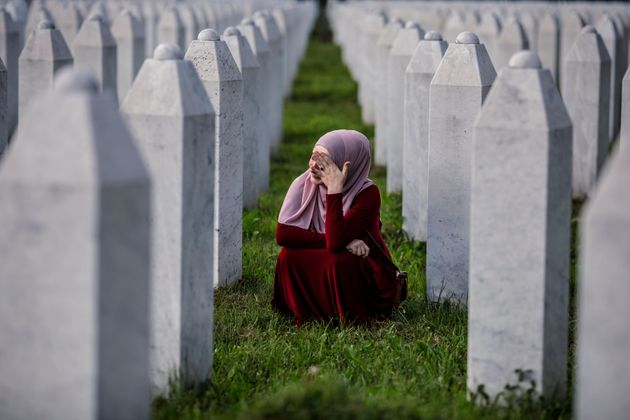 SREBRENICA, BOSNIA AND HERCEGOVINA - JULY 10: A Bosnian Muslim woman cries between graves of her father,...