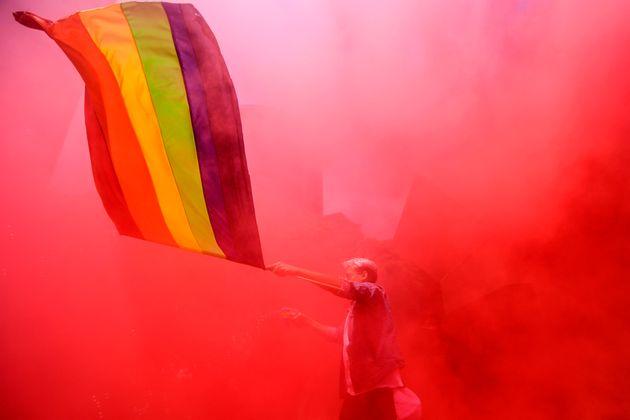 Un hombre porta la bandera arcoiris durante la marcha del Orgullo en