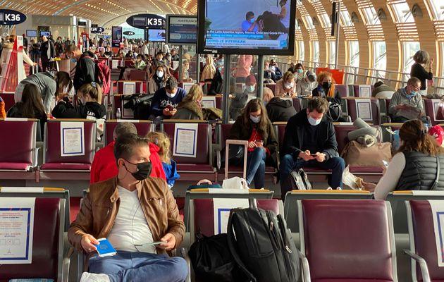 Passagers en salle d'attente occupant un siège sur deux à l'aéroport de Roissy,...