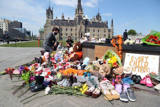 Justin Trudeau se arrodilla ante el memorial por los niños indios improvisado ante el Parlamento,...