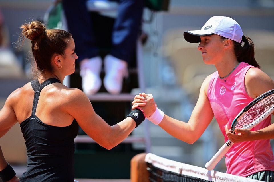 Greece's Maria Sakkari (L) and Poland's Iga Swiatek shake hands at the end of their women's singles quarter-final...