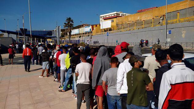 Inmigrantes marroquíes hacen cola ante la oficina de Asilo y Refugio de la frontera del Tarajal, en