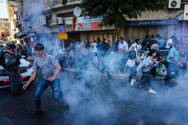 Israeli security forces throw stun grenades Sunday to disperse a crowd gathered for a news conference calling for the release