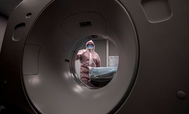 A medical worker wearing protective equipment stands by a computed tomography (CT) scanner at a new hospital...